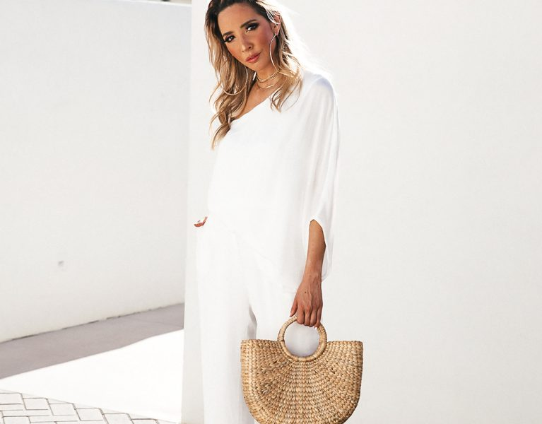 One shoulder white jumpsuit with basket bag, hoop earrings in Palm springs for a summer vacation outfit inspiration